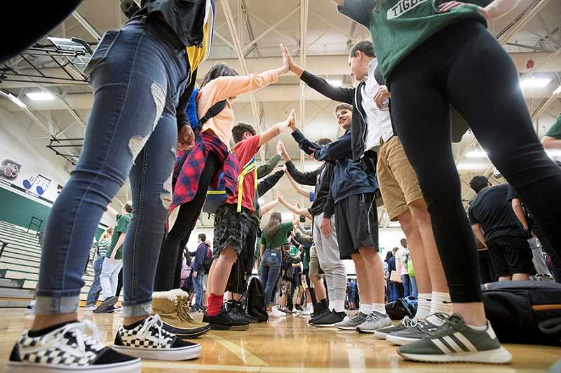 TIMES PHOTO: JAIME VALDEZ - Freshmen students high five each other during an assembly  held Tuesday at Tigard High School. The new students will have to contend with remodeling and construction projects throughout the school year.