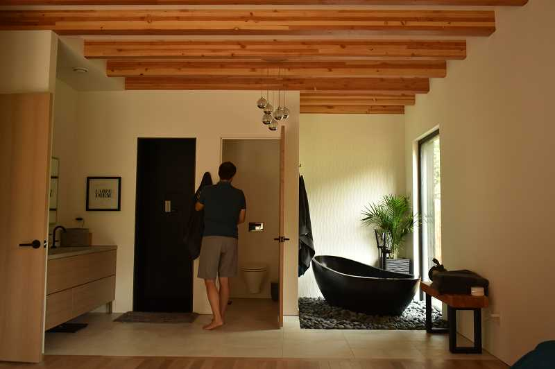 REVIEW PHOTO: LUCY KLEINER - One of the goals for Denise and Eric Antonini was to design a bedroom that doubled as a sanctuary. The solid rock bathtub to Eric's right accents the bathroom that opens to the master bedroom.