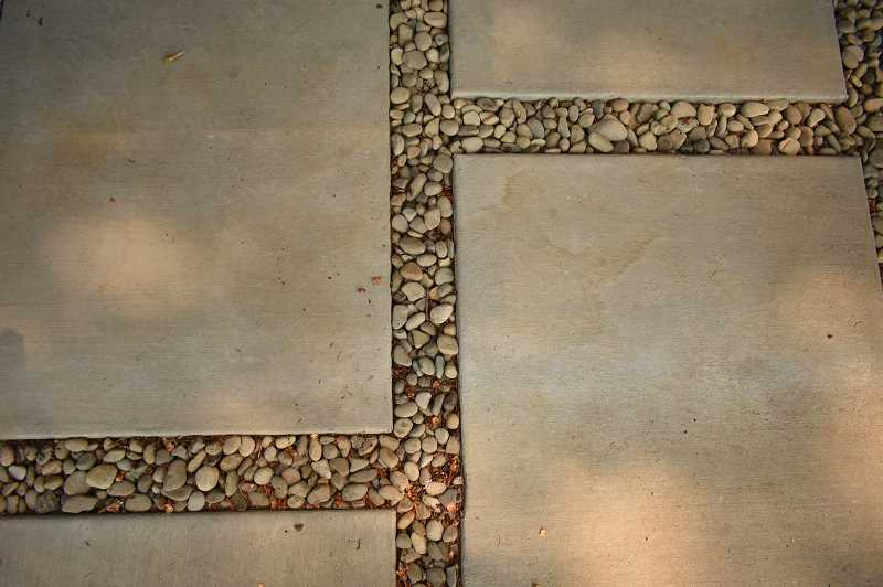 REVIEW PHOTO: LUCY KLEINER - River rock lines the Antonini home to collect stormwater runoff.