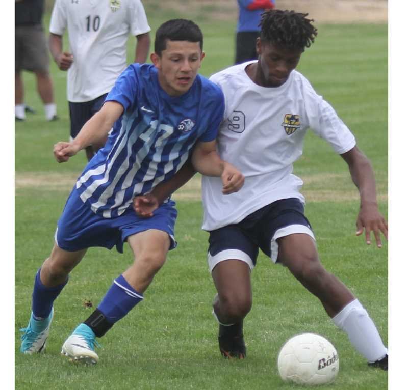 STEELE HAUGEN/MADRAS PIONEER - Zachary Guthrie and Angel Solis of Madras fight for a ball Thursday afternoon in a non-league soccer match. The White Buffalos dominated the match, winning 9-1.