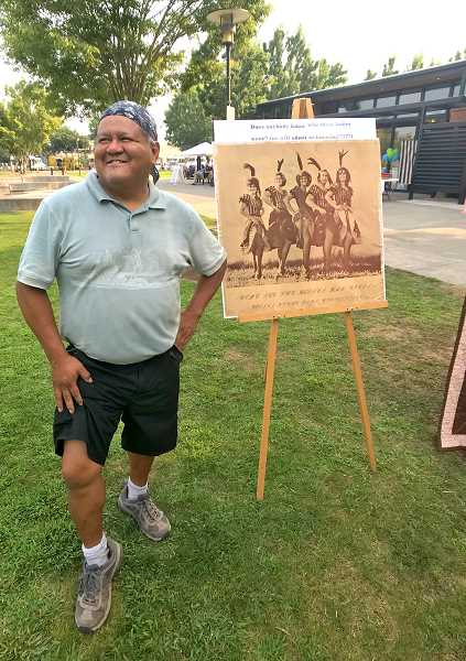 SPOKESMAN PHOTO: LESLIE PUGMIRE HOLE - WBFHS temporary archivist, Creston Smith, has fun with a vintage poster at Wilsonvilles 50th birthday party Aug. 22.