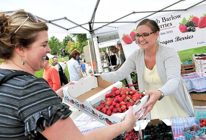 Maria Martishev of South Barlow farm in Canby sells a flat of strawberries.
