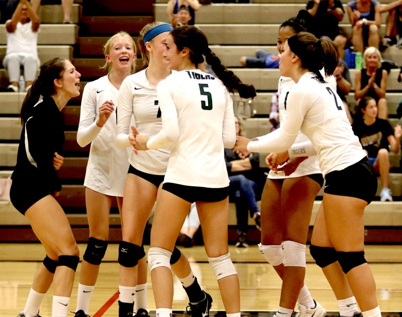 TIIMES PHOTO: DAN BROOD - Members of the Tigard volleyball team celebrate following their first-set victory in Tuesdays match at Tualatin.