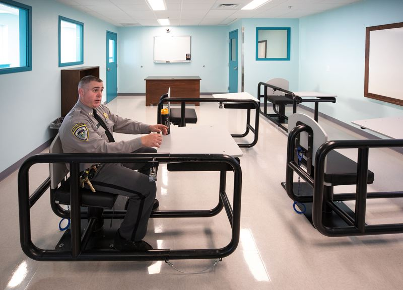 JONATHAN HOUSE/PAMPLIN FILE PHOTO - Correctional Capt. Toby Tooley demonstrates how the desks work at a behavioral health treatment center that opened in August at Oregon State Penitentiary in Salem.
