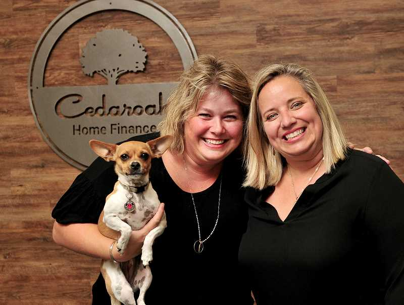 STAFF PHOTO: VERN UYETAKE  - Iris, the office dog, and Katie Walsh, left, pose with Whitney Hogue in Cedaroak Home Finances offices in West Linn.