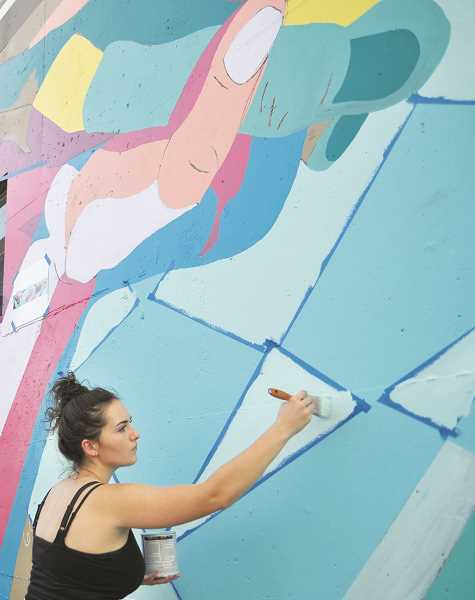 SETH GORDON - George Fox University junior Annabelle Wombacher works on the Yamhill County Mural Project's first-ever installation at Steve's Auto Repair in downtown Newberg.