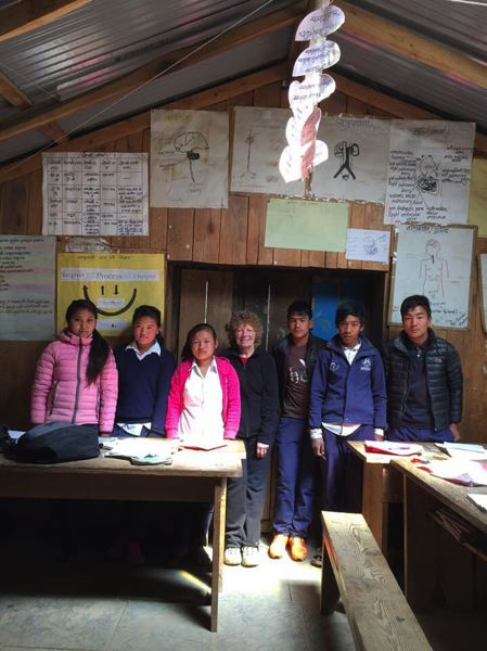 PHOTO COURTESY OF ROSEMARY JEFFREY - Rosemary Jeffrey, center, smiles with a group of students at the Sherpa school she regularly visits when she treks in Nepal. Jeffrey has been visiting the school for years and helps teach English and works with locals when shes there.