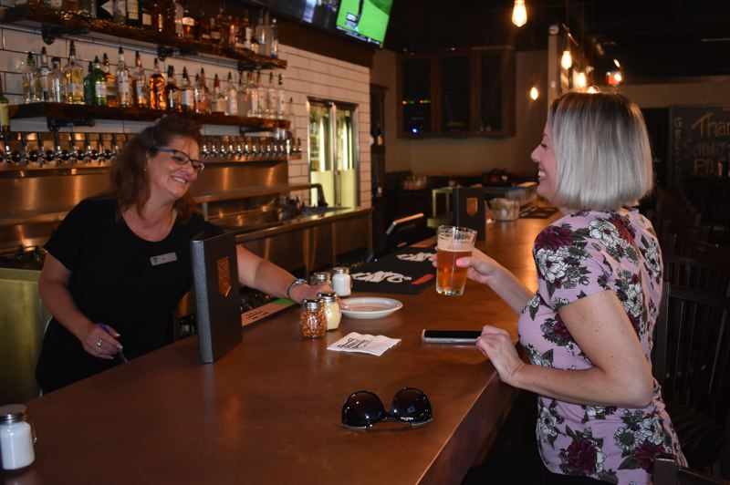 OUTLOOK PHOTO: SHANNON O. WELLS - Bartender Jill Mason, a Gresham resident, interacts with customer Shannon Pierce, who stopped into the new pub for the first time while shopping at Gresham Town Fair.