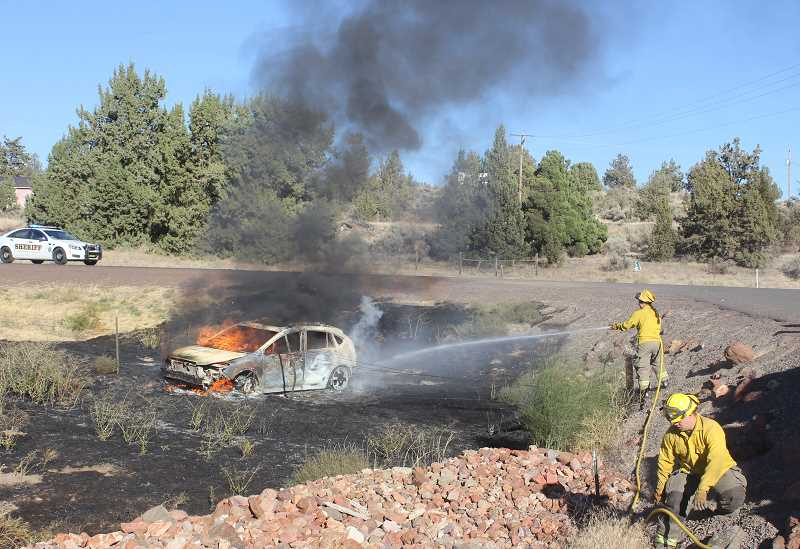 SUSAN MATHENY/MADRAS PIONEER - Firefighters douse the Subaru, which left the road and caught fire at U.S. Highway 97 and NE Elm Lane, five miles north of Madras.