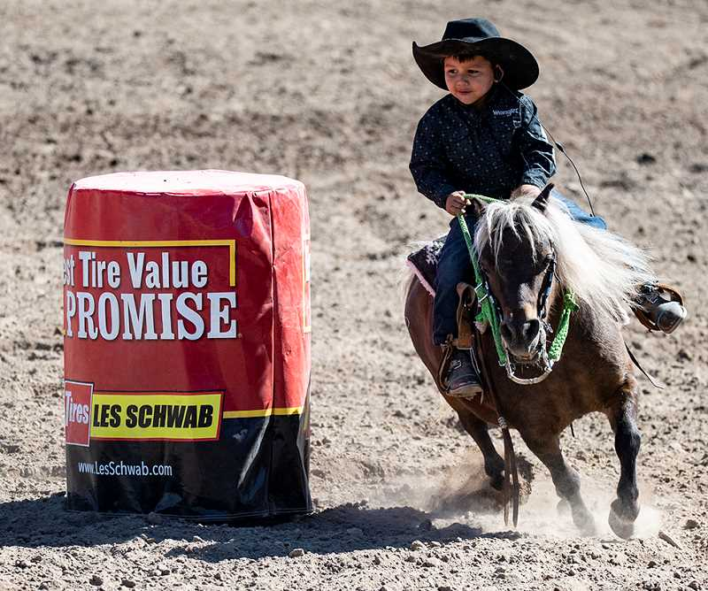 LON AUSTIN/CENTRAL OREGONIAN - Boots Raccoon makes a barrel racing run on his pony. Raccoon finished with a time of 24.29.