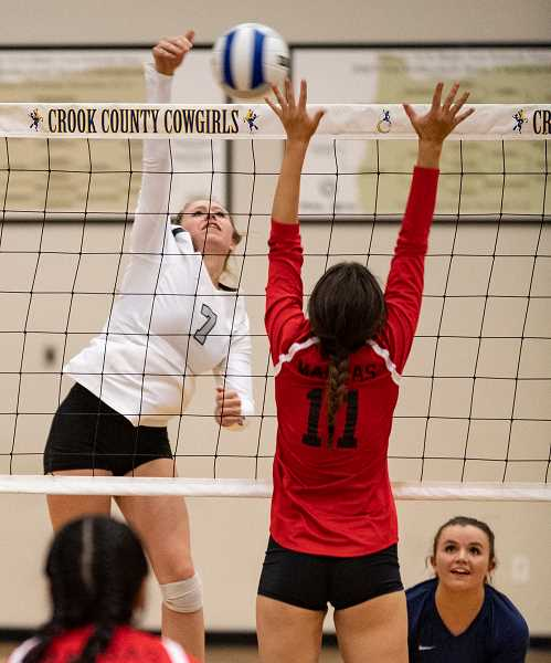 LON AUSTIN/CENTRAL OREGONIAN - Lily Cooper goes up for one of her five kills against Madras while libero Mekynzie Wells covers for her. The Cowgirls won the match in straight sets.