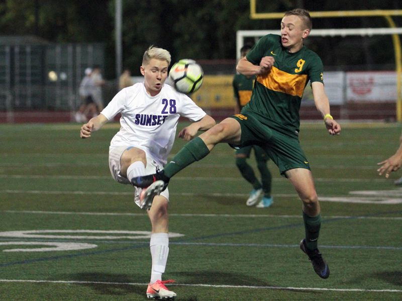 TIDINGS PHOTO: MILES VANCE - West Linn's Kyle Gregg (right) challenges Sunset's Ethan Dull for the ball during the Lions' 2-0 win at West Linn High School on Thursday.