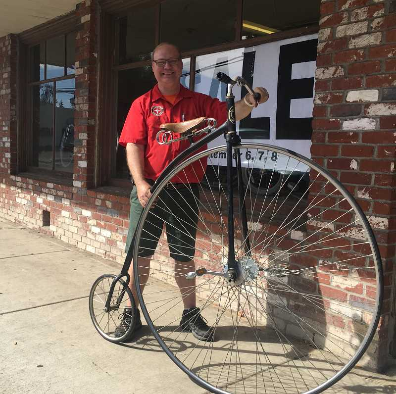 STAFF PHOTO: JANAE EASLON - Justin Schlegel poses with a bike from the 1890s in front of his family's shop, Schlegel's Bicycle Center.