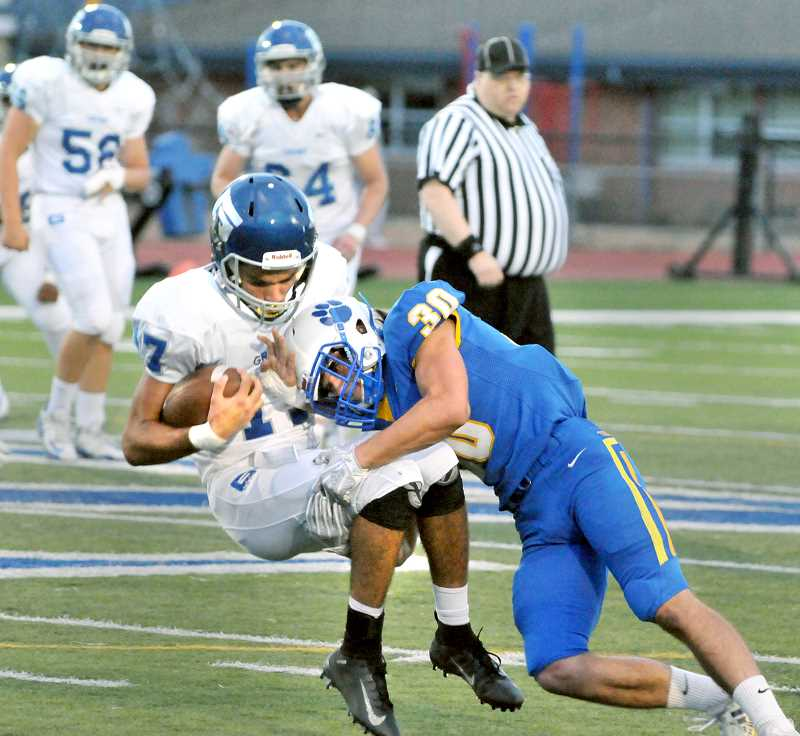 SETH GORDON - Newberg ? ? brings down a Grant runningback in the Tigers' ?-? win Friday at Loran Douglas Field. The win leveled NHS' season record at 1-1 in the second week of play.