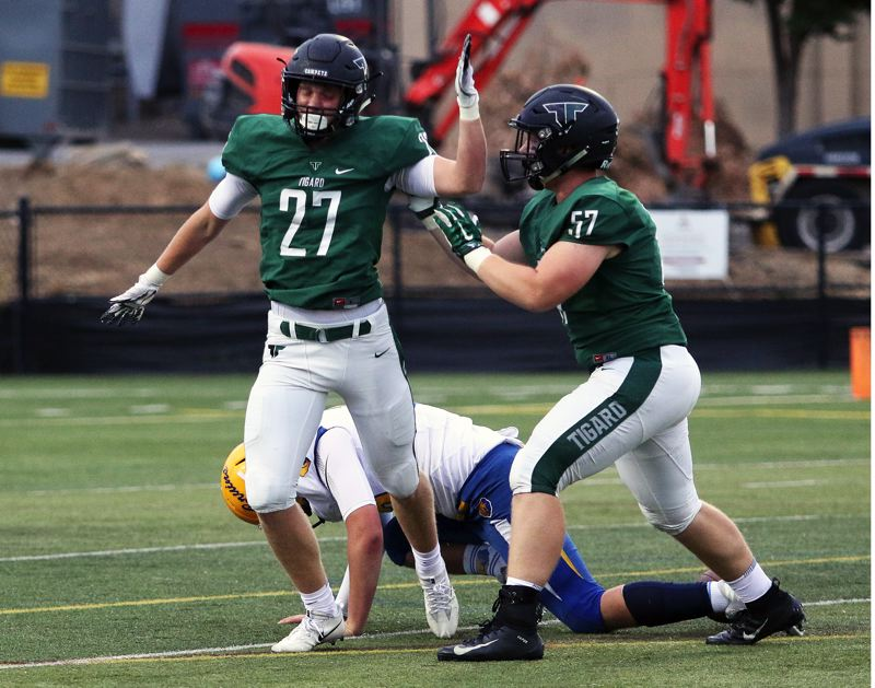 TIMES PHOTO: DAN BROOD - Tigard junior Fletcher Ahl (27) celebrates with senior Carter Dennis after making a quarterback sack during the Tigers' 58-14 win over Barlow on Friday.