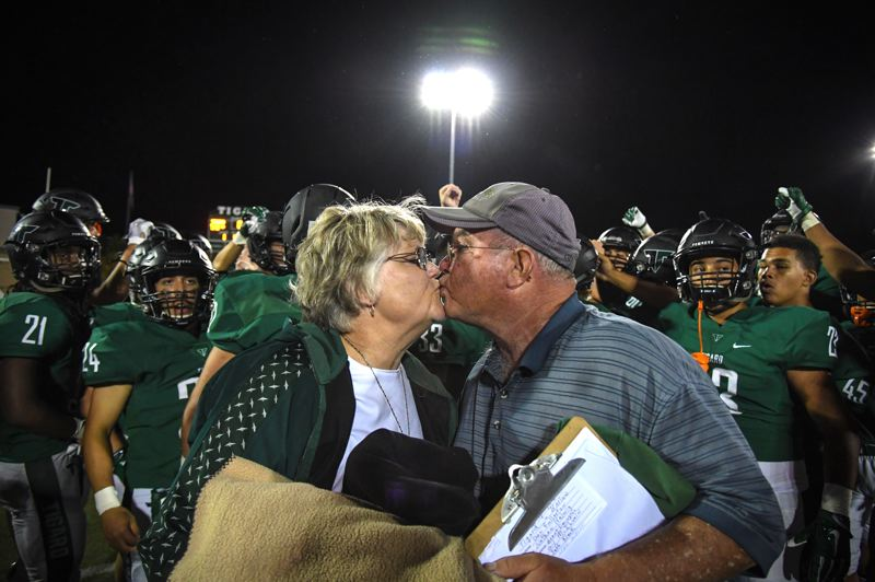 PHOTO COURTESY OF RALPH GREENE - Tigard coach Craig Ruecker gets a kiss from his wife, Beverly, following the Tigers' 58-14 win over Barlow on Friday. The victory marked Ruecker's 300th coaching win.