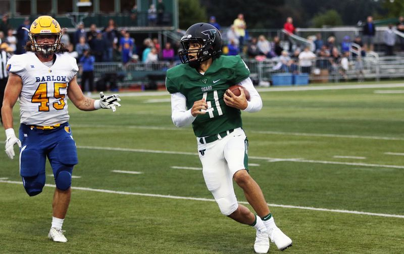 TIMES PHOTO: DAN BROOD - Tigard junior quarterback Drew Carter (41) scrambles for yardage during the 58-14 win over Barlow on Friday.