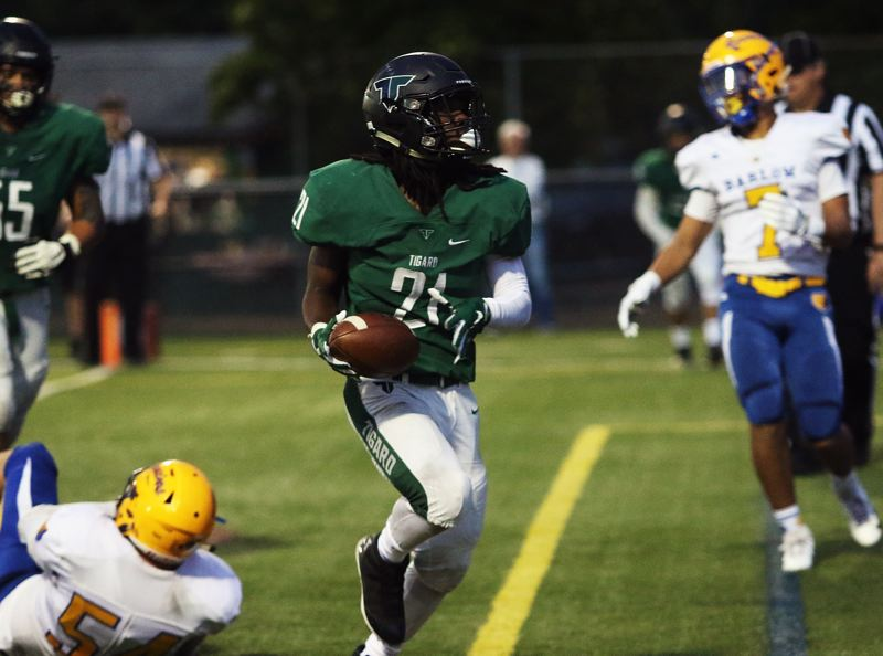 TIMES PHOTO: DAN BROOD - Tigard senior Malcolm Stockdale scores one of his four first-half touchdowns during the Tigers' 58-14 win over Barlow on Friday.