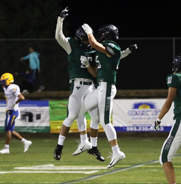 TIMES PHOTO: DAN BROOD - Tigard's Jazz Ross (left) and Spencer Kuffel celebrate following Ross' 77-yard touchdown catch during Friday's game.