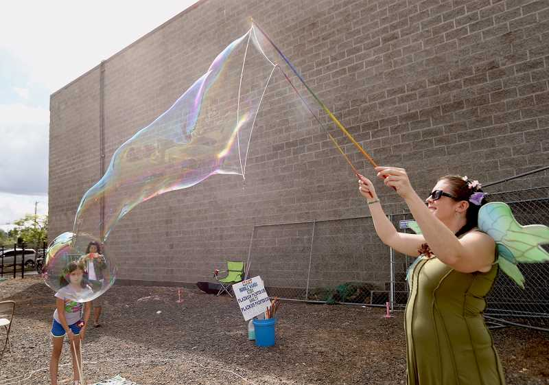 TIMES PHOTO: JAIME VALDEZ -  The Traveling Bubble Fairy, aka Ashley Blose, demostrates how to make huge soap bubbles using her special wand during the  7th Annual Explore Downtown Tigard Street Fair and Latino Festival held Saturday.