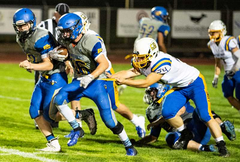 Kaden Horton goes up the middle for a big gain during the Cowboys Friday night game against Cottage Grove. Horton carried the ball eight times for 70 yards to lead the Cowboys in rushing yardage.