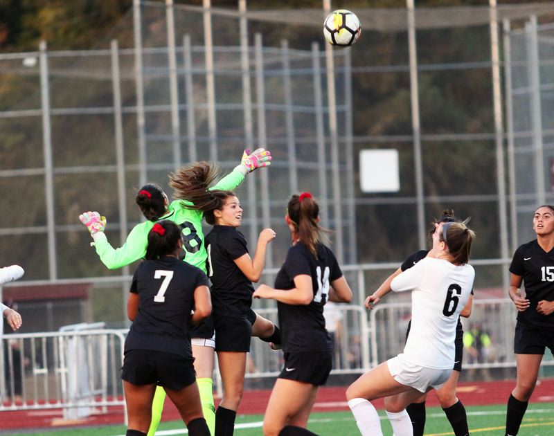TIMES PHOTO: DAN BROOD - Sherwood freshman goalkeeper Tali Kozma (left) and junior defender Jillian Leroux knock the ball away on a Tualatin corner kick.