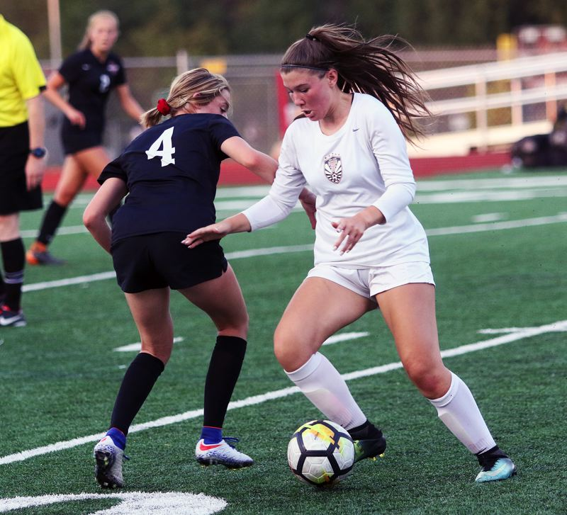TIMES PHOTO: DAN BROOD - Tualatin senior Skylar Maddox (right) looks to move past Sherwood junior Ava Boughey during Thursdays match.