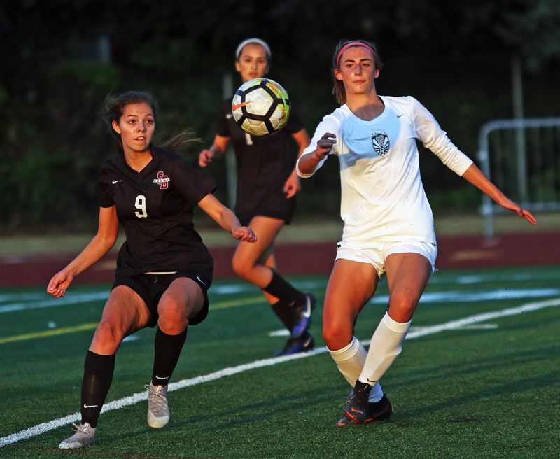 TIMES PHOTO: DAN BROOD - Sherwood junior Jillian Leroux (left) and Tualatin junior Abby Borg eye the ball during Thursday's match.