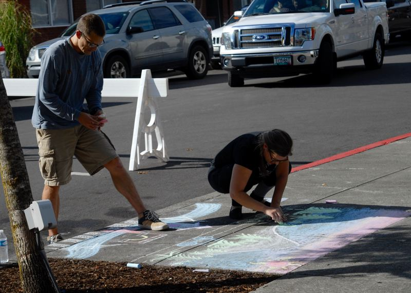 OUTLOOK PHOTO: MATT DEBOW  - Megan and Tim Hanson decorate a square of sidewalk during the Chalk the Walk competition during Fairviews 12th annual Fairview on the Green Celebration on Saturday, Sept. 8.