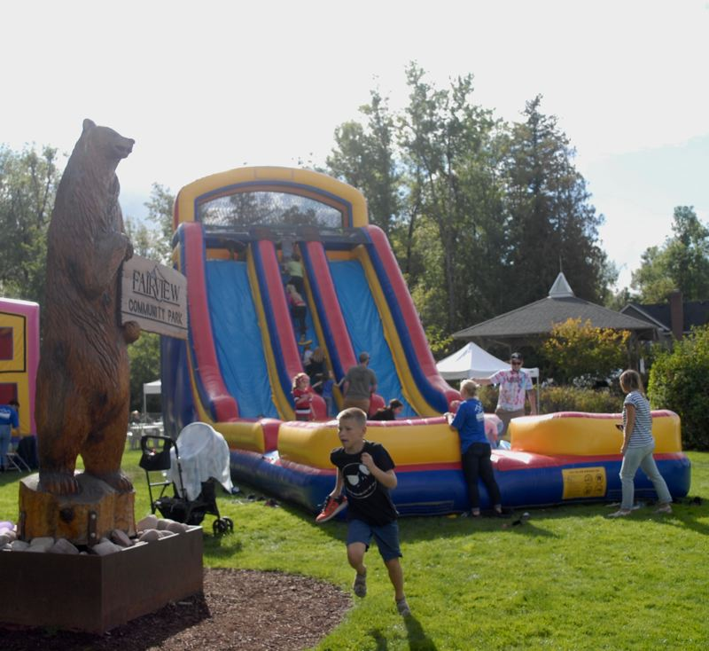 OUTLOOK PHOTO: MATT DEBOW  - Kids slide down a large bounce during Fairviews 12th annual Fairview on the Green Celebration on Saturday, Sept. 8.