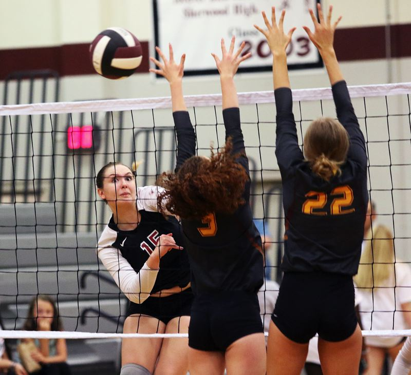 TIMES PHOTO: DAN BROOD - Sherwood High School senior Alyssa Haslip (left) smacks the ball over the net during the first set of the teams sweep against Forest Grove on Monday.