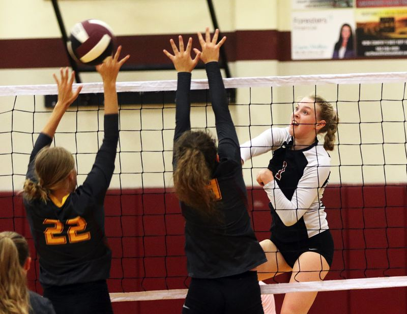 TIMES PHOTO: DAN BROOD - Sherwood junior Alli Douglass (right) hits a ball over the net during the Lady Bowmen's victory over Forest Grove on Monday.