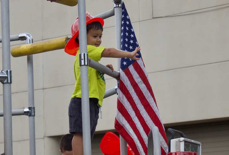 OUTLOOK PHOTO: CHRISTOPHER KEIZUR - A young Gresham citizen waves to his family from atop one of Gresham Fire and Emergency Services engines.