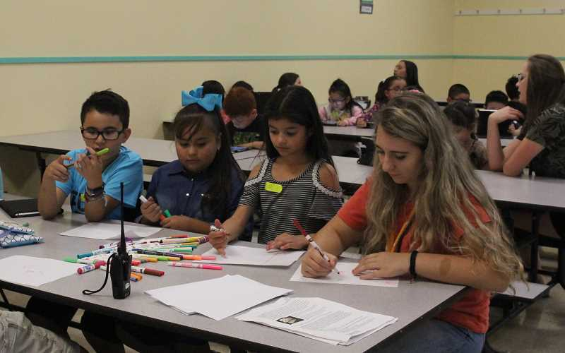 LINDSAY KEEFER - (From left) Giovanni Alvarado, Cassandra Gonzalez and Melanie Rios are students in Lincoln Elementary School's After School Club. They work on an arts project with staff member Nola Waage.