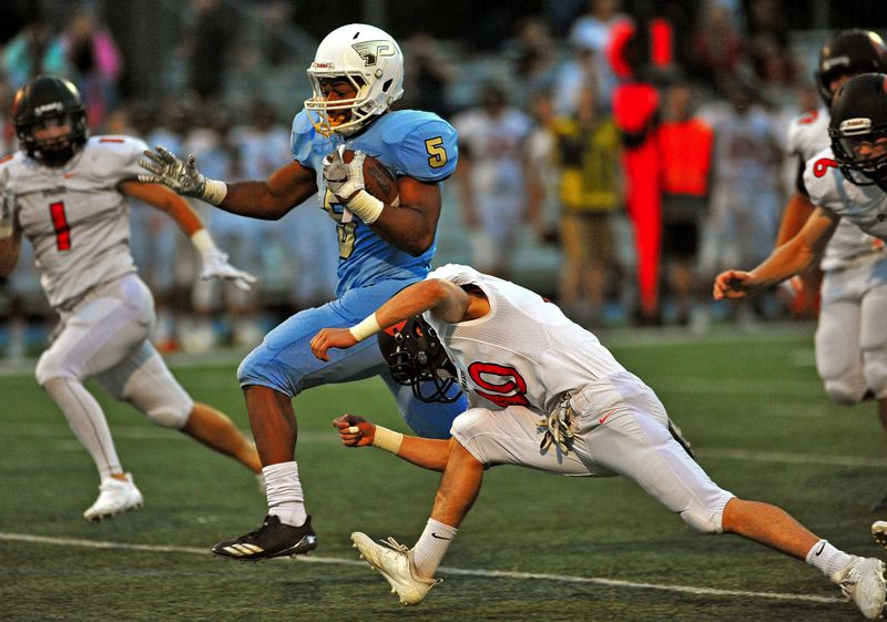 REVIEW PHOTO: JALEN JOHN - Lakeridge junior running back Jalen John breaks a tackle en route to some of his 130 rushing yards against Sprague on Friday night.