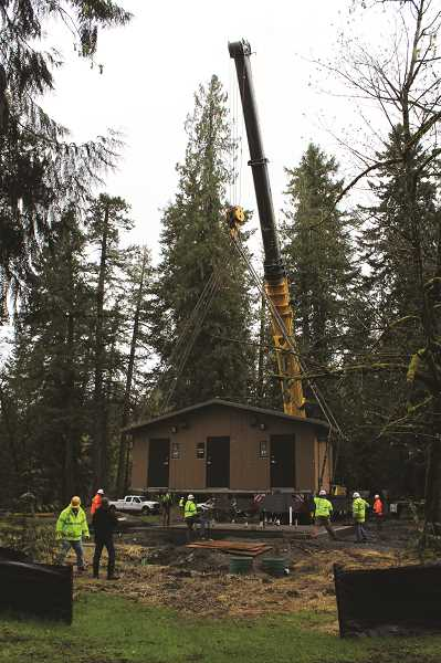 PIONEER PHOTO: KRISTEN WOHLERS - Clackamas County Parks and crews lower new restrooms in place at Feyrer Park in April.