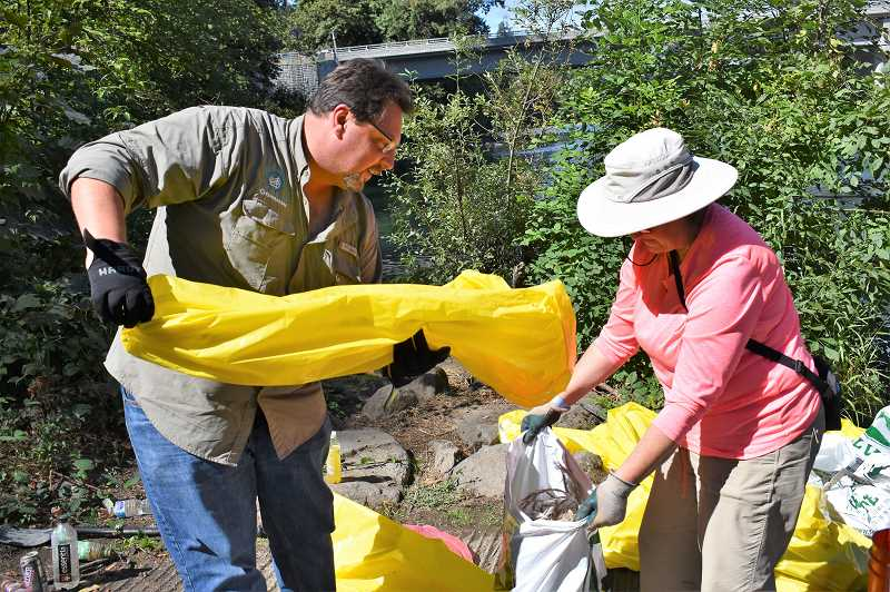 ESTACADA NEWS PHOTO: EMILY LINDSTRAND - John and Joyce Nagy sort through trash at Carver Park during the Down the River Cleanup on Sunday, Aug. 9.