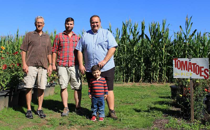 REVIEW PHOTO: SAM STITES - Stafford Family Festival Committee Chair Bill Markt, Cole Fiala, Rich Fiala and his grandson Anson pose for a photo near the u-pick tomatoes and corn maze at Fiala Farms.