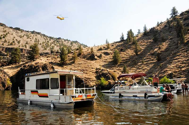 PHOTO BY TOM BROWN - Boats beach in a shallow area of Lake Simtustus on Saturday, as boaters watch a Chinook helicopter drpping water to fight the Willow Fire.