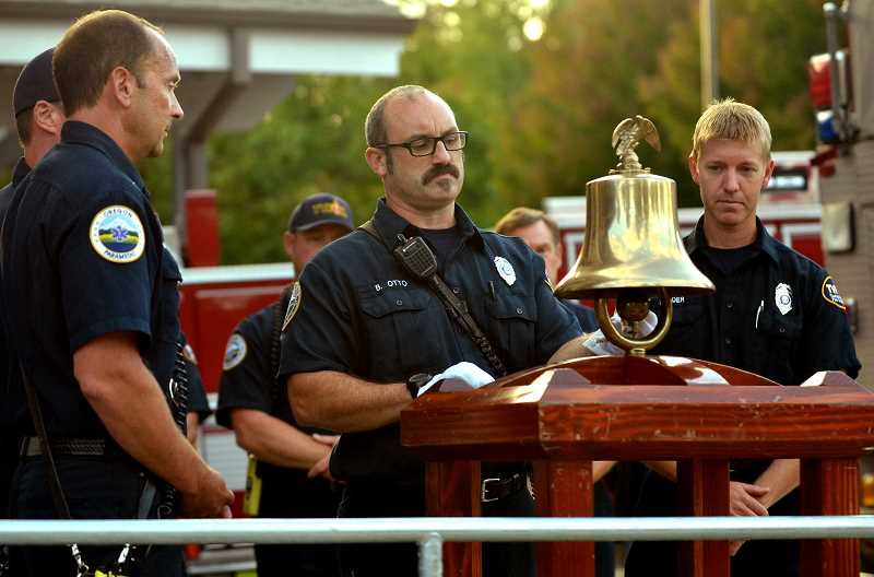 TIDINGS PHOTO: VERN UYETAKE  - Firefighter Benji Otto rings the firebell signaling the message of a lost firefighter.