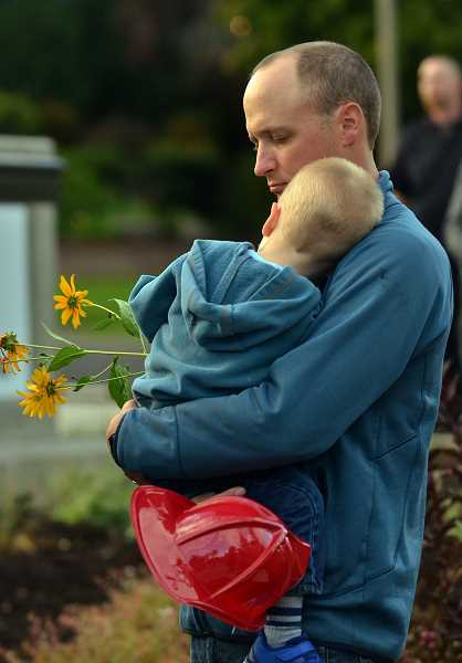 TIDINGS PHOTO: VERN UYETAKE  - Dan and his son Henry Sizemore observed a moment of silence.