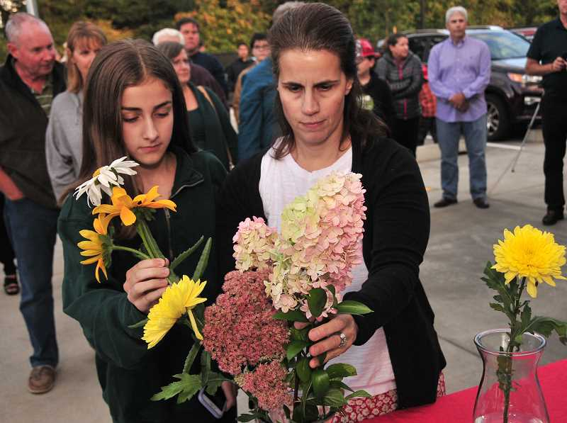 TIDINGS PHOTO: VERN UYETAKE  - Molly and Katie Bell add their flowers to the bouquets that will be displayed at the fire stations.