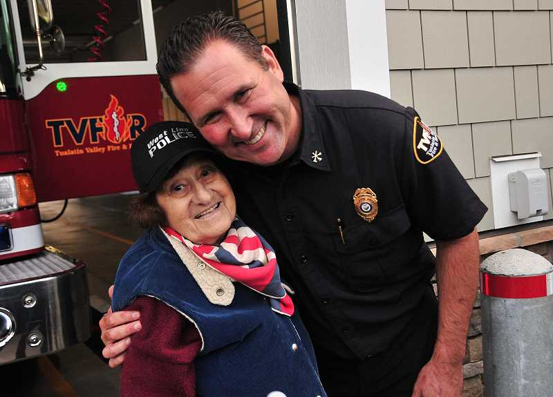 TIDINGS PHOTO: VERN UYETAKE - Alice Richmond gets a hug from firefighter Brian Sheppard.