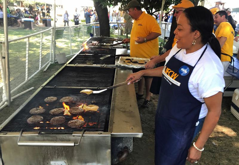 PAMPLIN MEDIA GROUP: DANA HAYNES  - Loretta Smith flips burgers at the United Food and Commercial Workers booth at the Labor Day picnic.