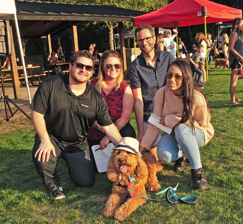 REVIEW PHOTO: VERN UYETAKE - Costume contest judges Sam Stites, Pearl Schwind, Joe Buck and Allysa Campos pose for a photo with Friday, the winner of the Barks & Brews costume contest