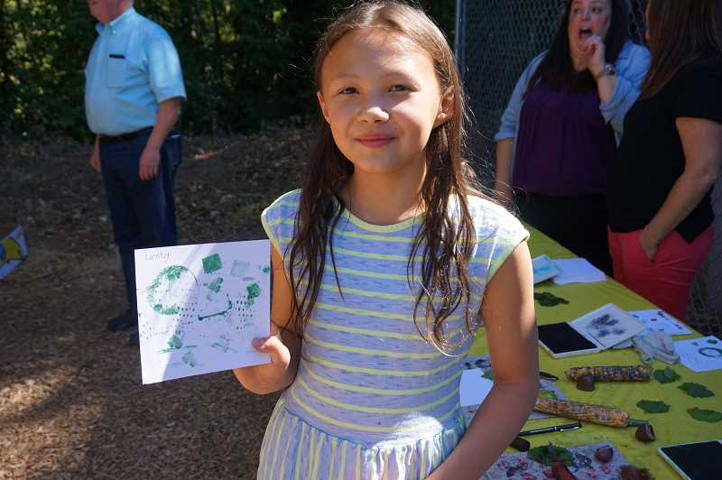 REVIEW PHOTO: CLAIRE HOLLEY - Hallinan student Cassey Koch shows off the art that she created using vegetables and an ink pad.