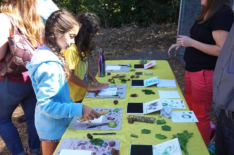 REVIEW PHOTO: CLAIRE HOLLEY - Malia McLaren and other Hallinan students create art using vegetables as stamps during Hallinan's annual Harvest Festival.