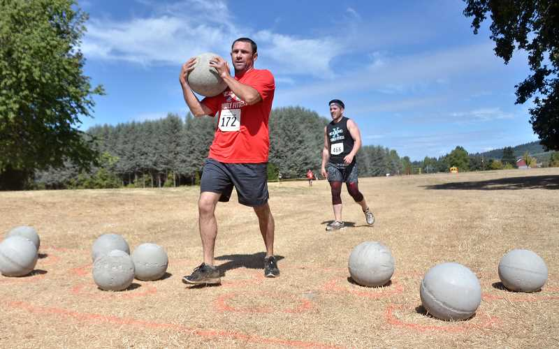 Jeff Jarman carries the weight ball through an obstacle at the Edge Familiy Fitness Run.