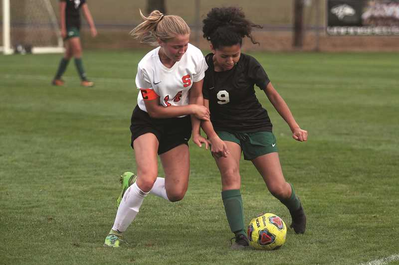 PAMPLIN MEDIA GROUP PHOTO: PHIL HAWKINS - North Marion senior Odallis Bedolla (right) fights for control of the ball against Scappoose junior Emma Jones in the second half of the Indians' 2-1 victory over the Huskies on Sept. 11.