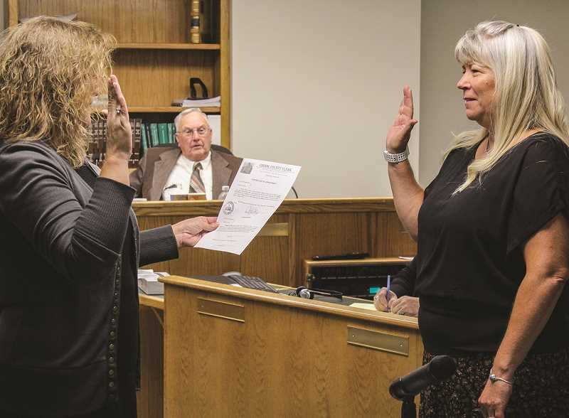 JASON CHANEY - Crook County Clerk Cheryl Seely (left) swears in new County Treasurer Debbie Palmer as County Commissioner Jerry Brummer looks on in the background.